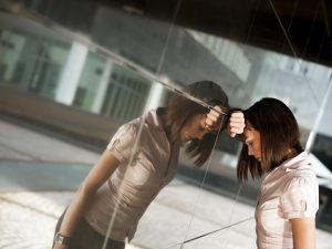 frustrated woman banging head against wall of office building