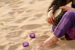 Hands of a woman holding a djembe on a sandy beach
