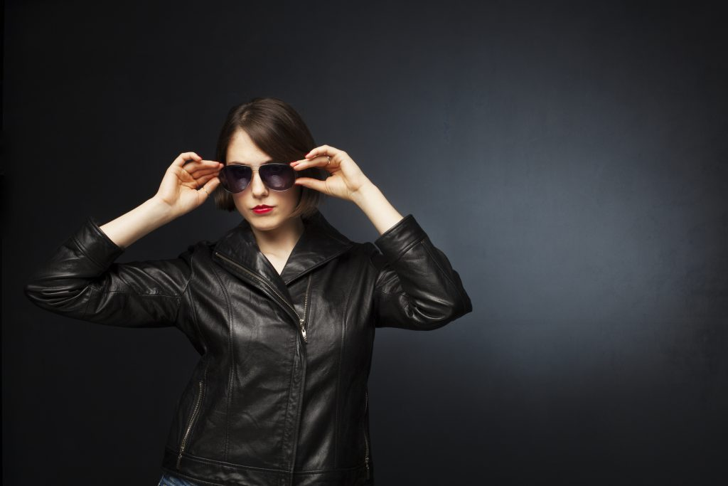 Portrait of a beautiful young woman on gray background, wearing leather jacket.